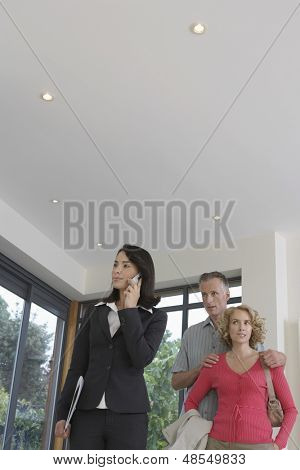 Young female real estate agent using mobile phone with couple observing new property