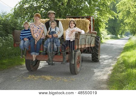 Full length portrait of couple with three kids sitting on back of trailer on country lane