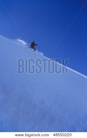 Side view of a person skiing down slope against clear blue sky