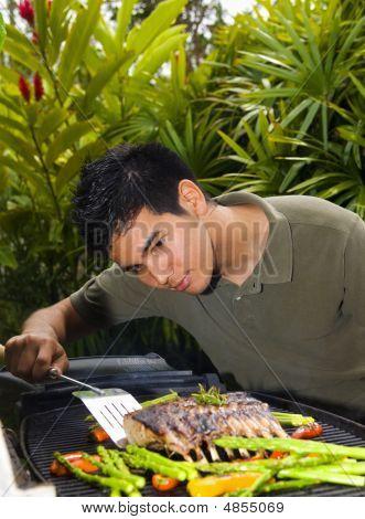 Hombre asiatico Carré de cordero asado a la parilla