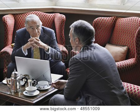 Two businessmen talking over laptop in office lobby