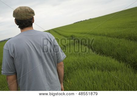 Rear view of a man standing in tilt field