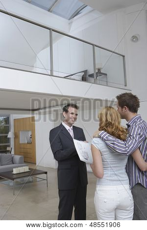 Friendly male real estate agent showing couple new home