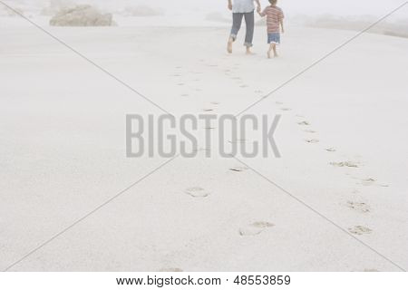 Rear view of father and son walking leaving behind footprints on sand at beach