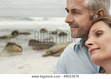 Closeup of romantic couple looking away at beach