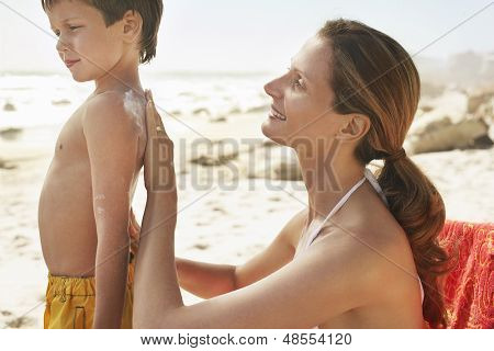 Side view mother applying sunscreen cream on son's back at beach
