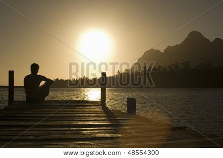 Rear view of man sitting on dock by lake enjoying sunset
