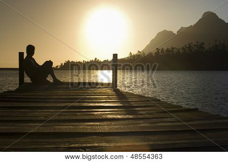 Side view of man sitting on dock by lake enjoying sunset