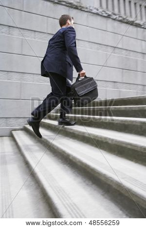 Full length side view of a businessman with briefcase ascending steps
