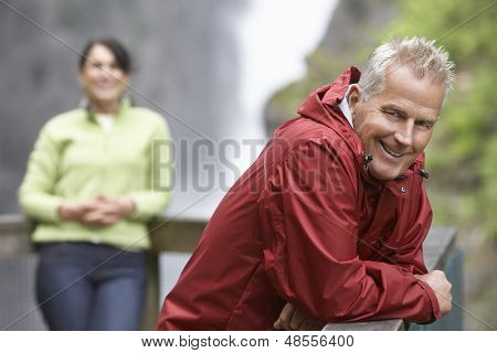 Smiling middle aged man with blurred woman in the background against waterfall
