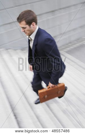 Full length of a businessman with briefcase ascending steps