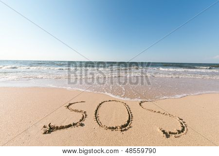 sea beach with sand word sos