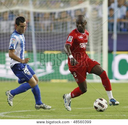 MALAGA, SPAIN. 19/09/2010. Juanmi the Malaga forward and Didier Zokora a Sevilla midfield player in action during the La Liga match between CF Malaga and Sevilla, played in the La Rosaleda Stadium
