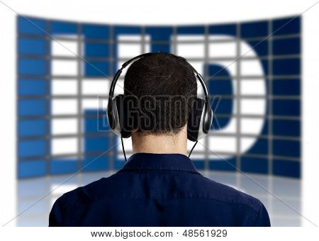 Back view of a young man with head phones watching a big TV panel