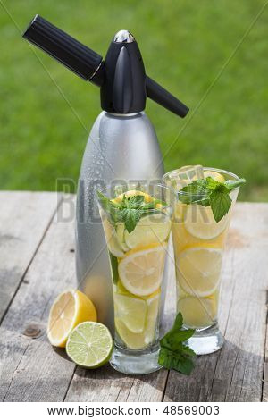Glasses with homemade lemonade and siphon on wooden table