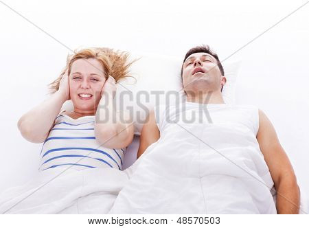 Snoring man, woman can not sleep, covering ears with pillow for snore noise