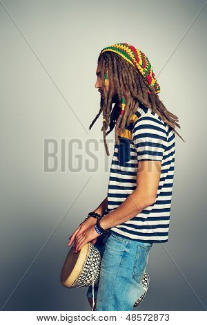 Portrait of a rastafarian young man playing his drum.