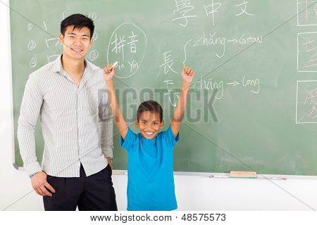 happy african boy with hands up after writing answer on chalkboard