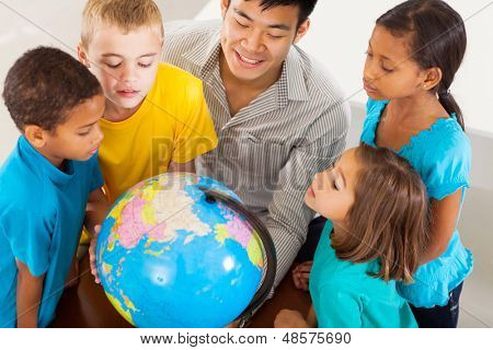 group of adorable students with teacher looking at the globe