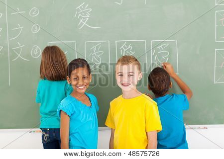 cheerful elementary school students after writing chines on chalkboard