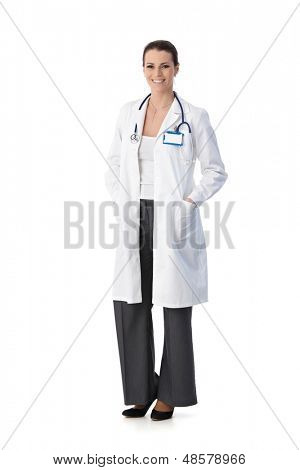 Full length portrait of happy female doctor standing in smock smiling at camera, cutout on white.