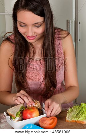 Smiling young woman preparing a lunchbox on the kitchen table