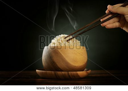 Cooked organic basmati brown rice in wooden bowl with human hand chopsticks and hot steam smoke on dining table. Low light setting.