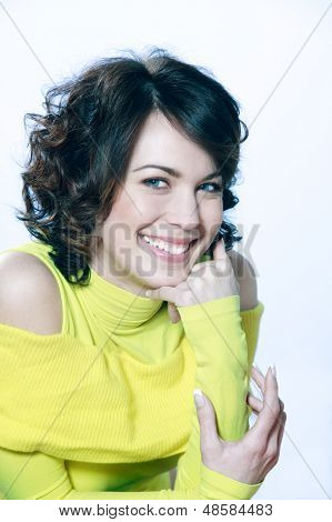 portrait in studio of a young caucasian  woman toothy smiling on blue background  a yellow sweater