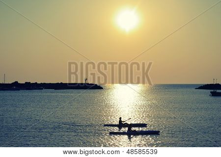 couple paddle together in summertime evening sea over sunset