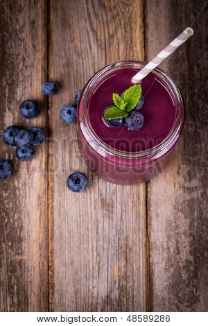 Blueberry smoothie in a glass jar with a straw and sprig of mint, over vintage wood table with fresh berries.