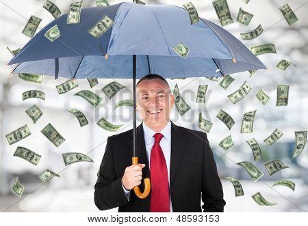 Happy man holding an umbrella in a money rain