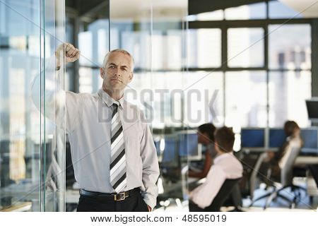 Confident middle aged businessman leaning on glass door with colleagues working in background