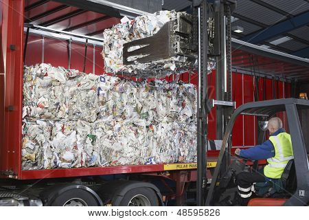 Worker in forklift truck loading stacks of recycled papers on to lorry