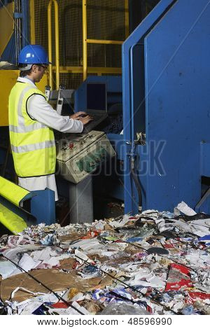 Side view of young worker operating conveyor belt in recycling factory