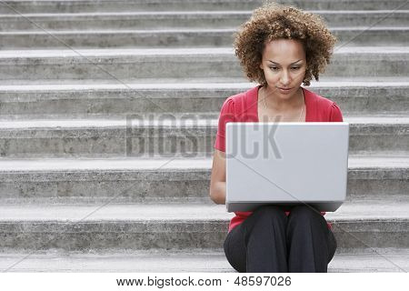 Young African American woman using laptop on steps outdoors
