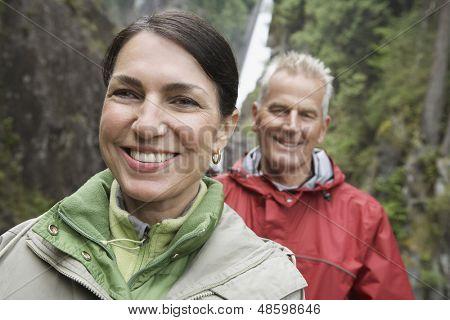 Closeup retrato de una mujer de mediana edad y mujer contra cascada sonriente