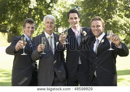 Portrait of happy four men toasting champagne flutes at wedding day