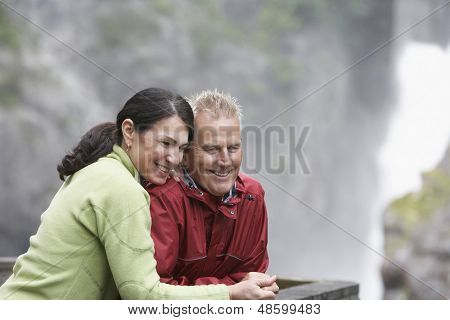 Happy middle aged man and woman looking at view against blurred background