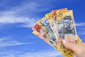 stock photo of wispy  - Handful of Australian money with blue sky background - JPG