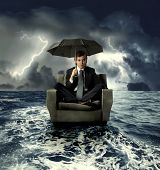 image of crisis  - businessman on an armchair lost in the sea - JPG
