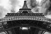 stock photo of arch foot  - perspective of the Eiffel tower from the bottom with a cloudy and bleak sky - JPG