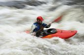 stock photo of canoe boat man  - Side view of a blurred man kayaking in rough river - JPG