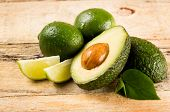 healthy food concept - avocado and lime slices on wooden background
