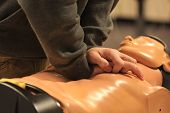 picture of cpr  - Image of rescuer practicing cpr on a dummy.