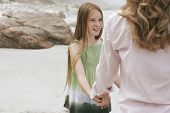 stock photo of preteen  - Happy preteen girl looking at mother while playing ring around the rosy on beach - JPG
