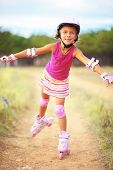 Cute child rollerskating outdoors in summer vacations