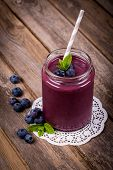 Blueberry smoothie in a glass jar with a straw and sprig of mint, over vintage wood table with fresh