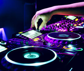 foto of disc jockey  - Dj mixes the track in the nightclub at a party - JPG