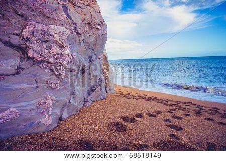 Footprints On The Beach By A Cliffside
