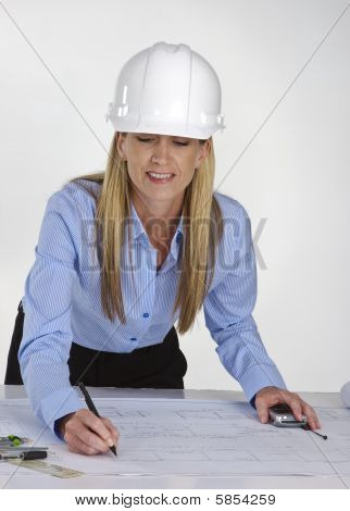 Female Architect Working On Blue Prints